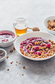 Granola with berry yoghurt, honey, chia seeds, raspberry sauce and fresh raspberries