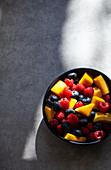 Bunter Obstsalat mit Mangostücken, Himbeeren und Blaubeeren