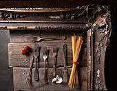 An arrangement of antique forks, spaghetti, garlic and tomatoes in a wooden frame
