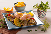 Poached salmon filet on a barley salad with oranges