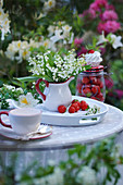 Maiglöckchenstrauß in Sahnekännchen auf Tablett mit Erdbeeren