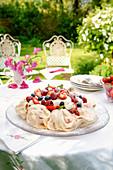 Leichtes Sommer-Pavlova auf Tisch im Garten