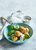 Gebratene Couscous-Gemüse-Bällchen mit Joghurtdip auf Spinat