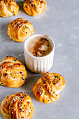 Vanilla knot buns with sesame and a cup of cappuccino