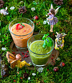 A kiwi smoothie and a strawberry smoothie in a fairy field