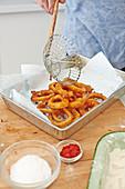 Frittierte Zwiebelringe zum Abtropfen auf Küchenpapier