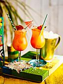 Rum Punch in Gläsern mit Cocktailschirmchen und Strohhalmen