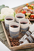 Mulled wine in four cups on wooden tray