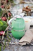 A green vintage thermos on a garden table
