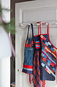 Patchwork aprons hung on a door