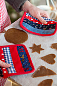 Hands holding a baking tray with gingerbread cookies with pot holder