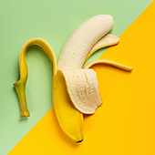 Half peeled banana on green and yellow background