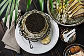 Schwarzer Kaviar in Dose auf Eis in silberner Schüssel serviert mit Champagner