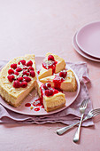 American baked cheesecake with fresh raspberries and raspberry sauce