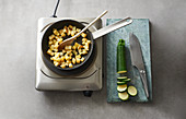 Diced potatoes being fried next to sliced courgettes