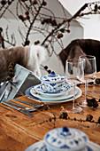 Blau-weiße Suppentassen mit Deckel an rustikalem Holztisch mit Weihnachtsdekoration