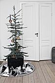 Geschmückter Baum im Korb und Geschenktütchen vor Zimmertür