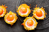 Fried potato straw cups with fried eggs and cheese