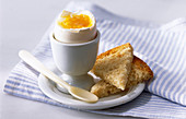 Breakfast egg in a cup and toast slices
