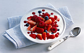 A bowl of yogurt with lots of red berries