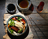 Bowl of Noodle Soup with Bok Choy, Cilantro, Enoki Mushrooms, Tofu, Snow Peas, Red Chili Peppers, Soy Sauce and Sesame Oil
