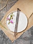 Orchid Flower on White Plate with Antique Chopsticks on Canvas Cloth