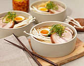 Bowls of Ramen Noodle Soup with Seasoned Egg, Pork, Enoki Mushrooms and Green Onions