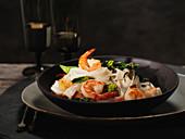 Asiatisches Nudelgericht mit Garnelen, Speck, Brokkoli und Tofu