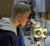 Student looking down a microscope