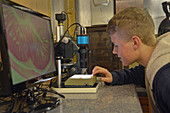 Teenager using a video microscope