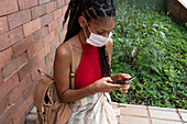Young woman in facemask using smartphone