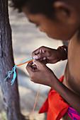 Wayuu indigenous child making bracelet, Colombia