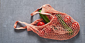 Tomatoes and cucumber in a shopping net