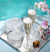 Poolside Champagne in two flutes on silver tray with ice bucket