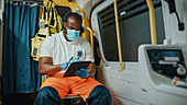 Paramedic in face mask using tablet while in ambulance