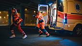 Team of paramedics treating injured patient in ambulance