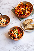 Oven baked beans with baked eggs, grated cheese and sourdough bread