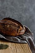 Selbstgemachtes Brot in Leinetuch auf rustikalem Holztisch