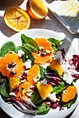 Salad with spinach, radicchio, orange, clementine, pistachios and feta