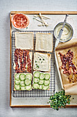Preparation of club sandwiches with bacon, cucumber and tomatoes
