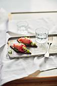 Pumpernickel canapes with salmon, avocado, wasabi and oregano