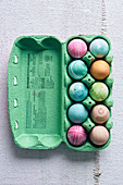 Colorful dyed Easter eggs in pastel colors in an egg carton