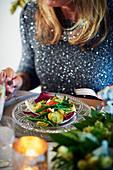 Frau isst festlichen Hummersalat mit Kartoffeln, Bohnen und Radicchio