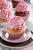 Muffins with rose cream decorated with sprinkles