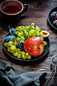 Plate with fruits - apple, blue grapes and plums
