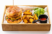 American chicken burger with potato wedges and tomato sauce