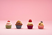 Various mini cupcakes against a pink background