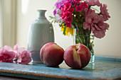 Pfirsiche auf einem Tablett mit Vasen und frischen Blumen