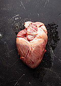 Raw whole beef heart on black stone background