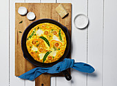 Overhead View of Egg Frittata with Tomato, Peas and Cheese In A Cast Iron Pan on Wood Cutting Board